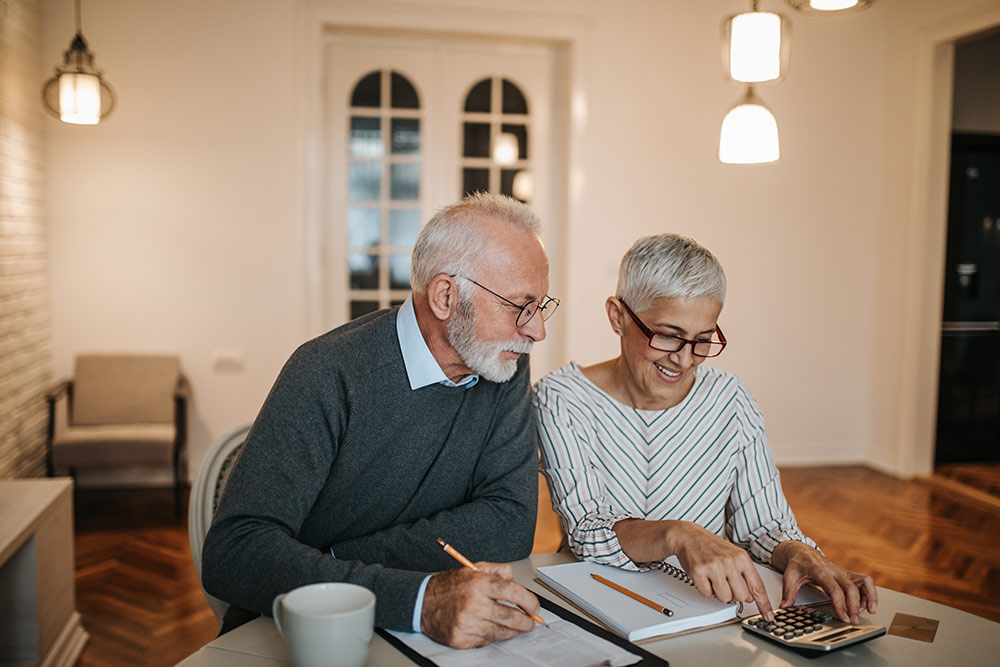 Senior couple looking over budget and expenses to save money for senior living